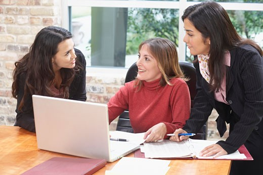 Three businesswomen in a discussion in an office : Stock Photo