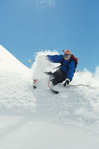 Stock Photo: 1598R-68108 Skier riding down powdery mountains
