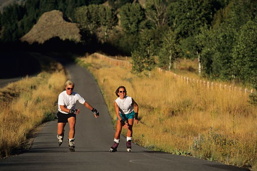 Stock Photo: 1598R-68235 Couple in-line skating on country road, Sun Valley, Idaho, USA