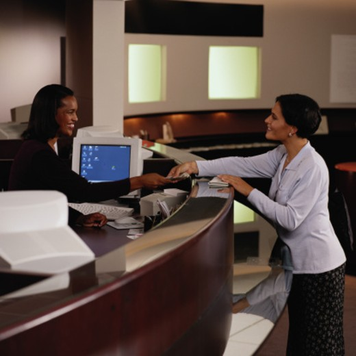 Stock Photo: 1598R-68531 Teller Handing Woman Money at a Bank