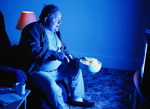 Man with Potato Chips and a Remote Control : Stock Photo