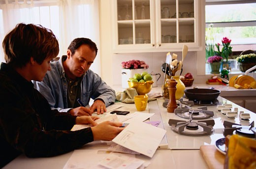 Couple Managing Their Finances in the Kitchen : Stock Photo