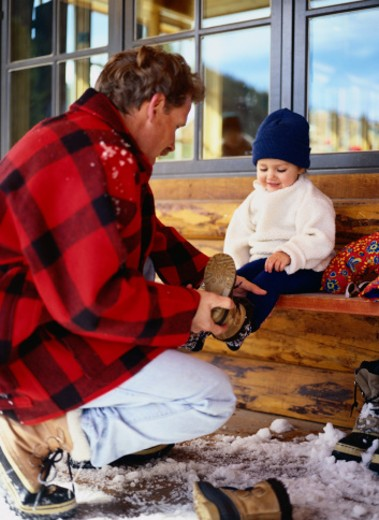 Stock Photo: 1598R-69893 Father Helping His Daughter Take Off Her Snow Boot