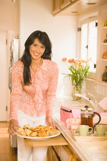 Young woman with pastries on platter in kitchen, smiling, portrait : Stock Photo