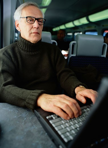 Businessman Working at a Laptop on a Train : Stock Photo