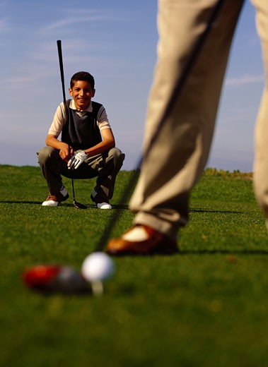 Boy Watching Father Tee Off : Stock Photo