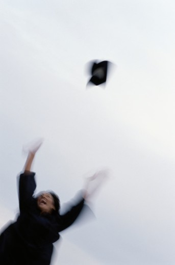 Joyful Graduate Tosses Mortar Board into Air : Stock Photo