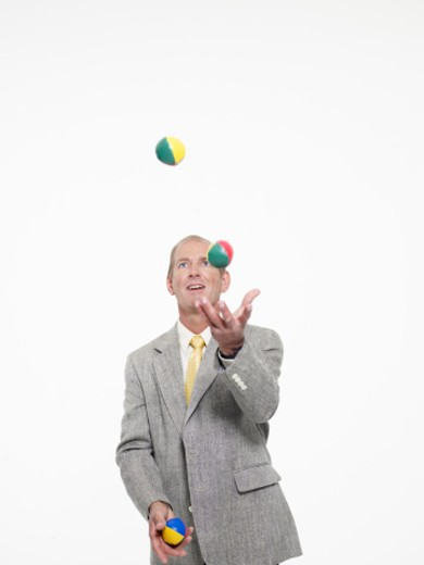 Stock Photo: 1598R-7425 Mature businessman juggling, smiling, close-up