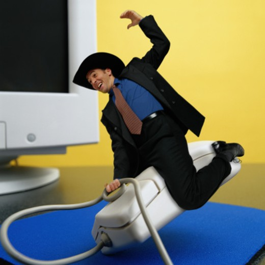 Stock Photo: 1598R-79429 Businessman Cowboy Riding Computer Mouse