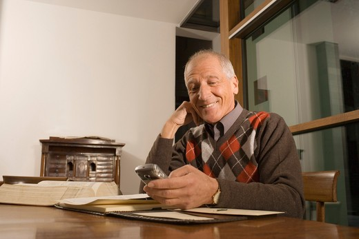 Mature man sitting at table looking at mobile phone, smiling : Stock Photo