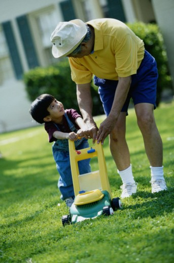 Grandfather and Grandson with Toy Lawnmower : Stock Photo