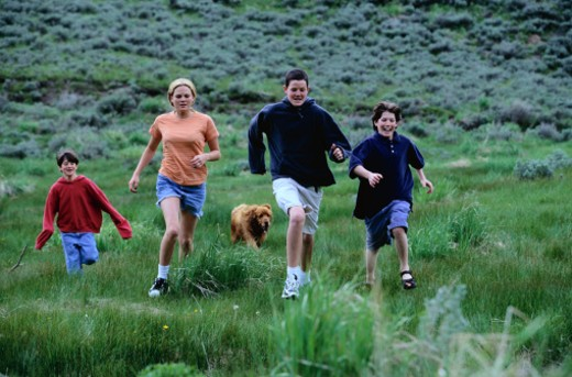 Stock Photo: 1598R-84172 Children Running with a Dog