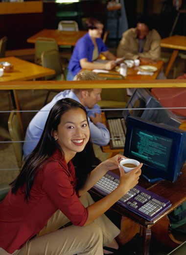 Stock Photo: 1598R-84328 Smiling Woman at a Cybercafe Computer