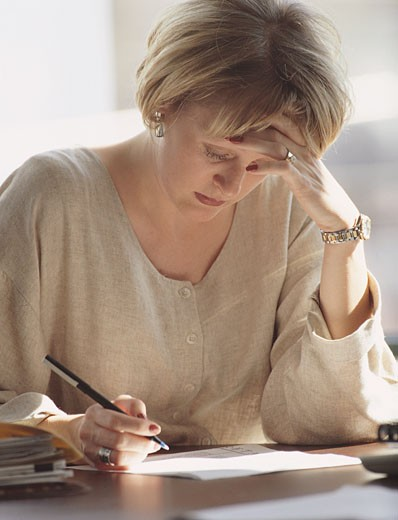 A BLONDE BUSINESSWOMAN DRESSED IN A CREAM COLORED SHIRT HOLDS A PEN AS SHE EDITS PAPERS : Stock Photo