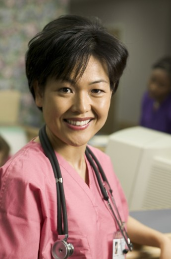 Stock Photo: 1598R-86683 portrait of an adult female in pink scrubs as she stands by the nurses station and smiles