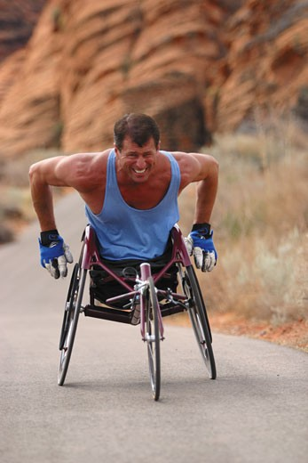 lifestyle photograph of a caucasian male wheelchair racer as he trains in a red rock canyon : Stock Photo