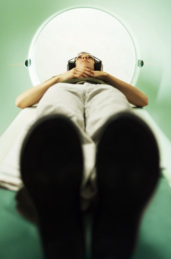 a young woman lays down as she prepares for a cat scan : Stock Photo