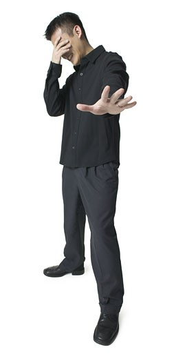 Stock Photo: 1598R-86892 an asian man dressed in black puts his hand to his face as if overcome with emotion