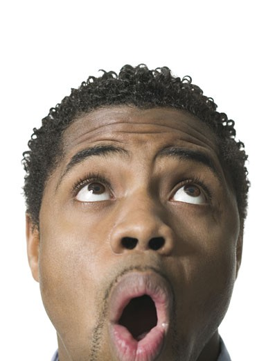 close up shot of a young adult male as he looks above his head and reacts with awe : Stock Photo