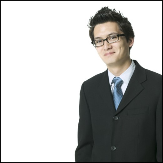medium shot of a young adult busines man in a dark suit and glasses as he looks confidently into the camera : Stock Photo