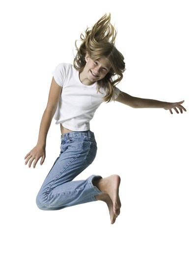 full length shot of a teenage female in jeans and a white shirt as she jumps through the air : Stock Photo