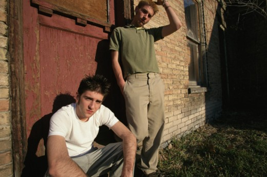 two teenage boys are outside an old abandoned building looking seriously int o the camera : Stock Photo