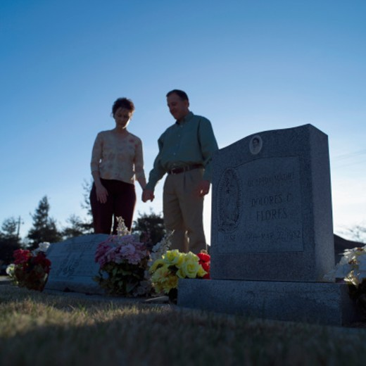 Man and woman holding hands in cemetery (focus on tombstone) : Stock Photo