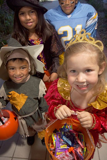 Children (4-8) in Halloween costumes trick-or-treating, elevated view : Stock Photo
