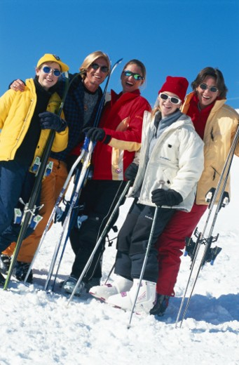 Young women holding ski gear, standing on slopes : Stock Photo