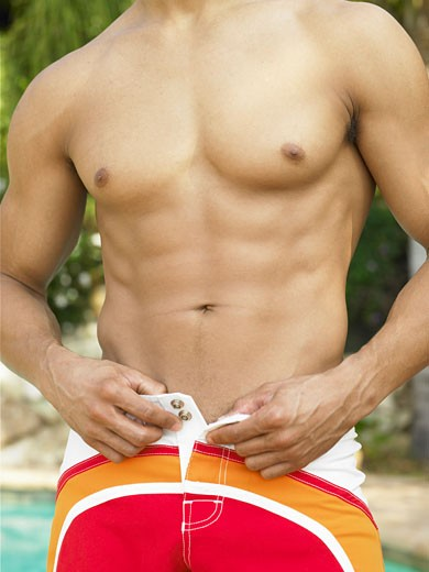 Stock Photo: 1598R-9264 Shirtless man removing swimming trunks, mid section