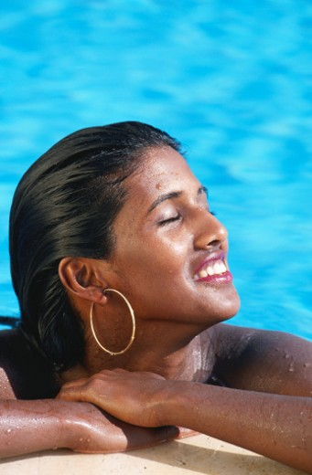 Stock Photo: 1598R-92892 Woman in swimming pool resting by the edge
