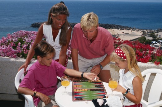 Family playing backgammon : Stock Photo