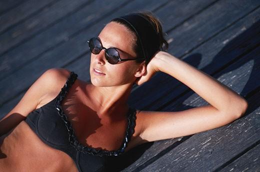 Woman lying on deck : Stock Photo