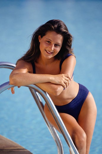 Young woman posing by pool ladder : Stock Photo