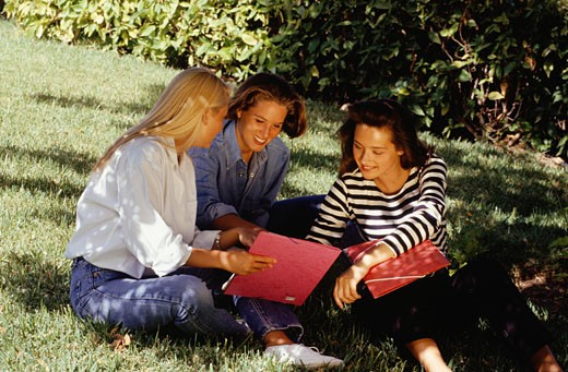 Stock Photo: 1598R-93563 Three young woman sitting on lawn in park