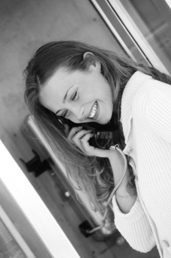 Young woman talking on pay phone (B&W) : Stock Photo