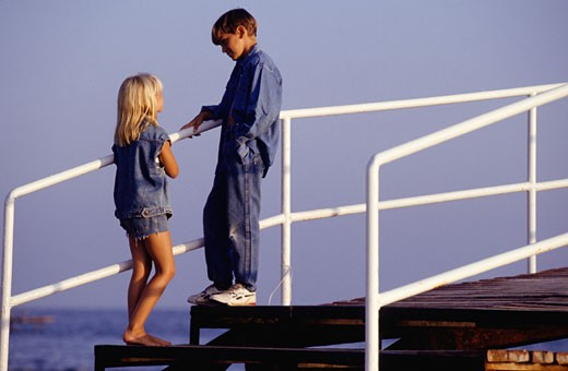 Boy and girl (8-9) standing on stairs by sea, side view : Stock Photo