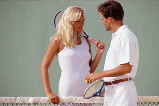 Young man and young woman talking on tennis court : Stock Photo