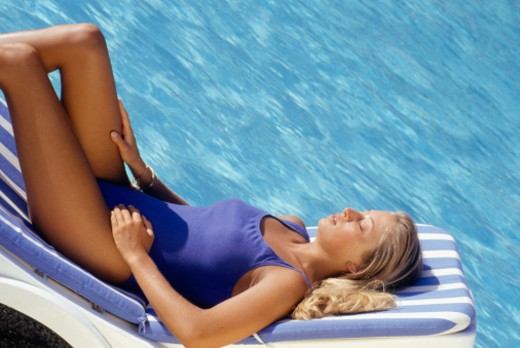 Young woman lying on sunlounger by pool, side view : Stock Photo
