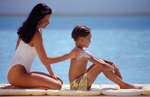 Mother applying sun cream on shoulder of son (8-9) by sea, side view : Stock Photo