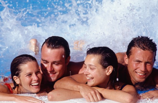 Two young couples enjoying themselves in swimming-pool : Stock Photo