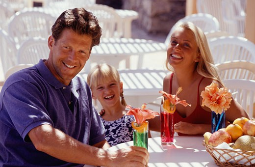 Parents with daughter (8-9 )sitting at table with cocktails, smiling : Stock Photo
