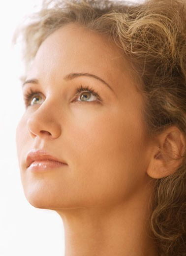 Young woman looking upward, side view, close-up : Stock Photo