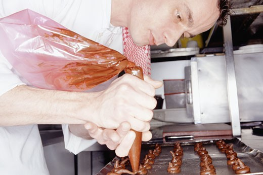 Chef making chocolates in kitchen : Stock Photo