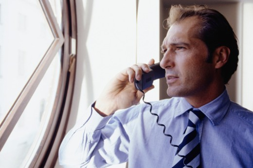 Businessman talking on phone by window : Stock Photo