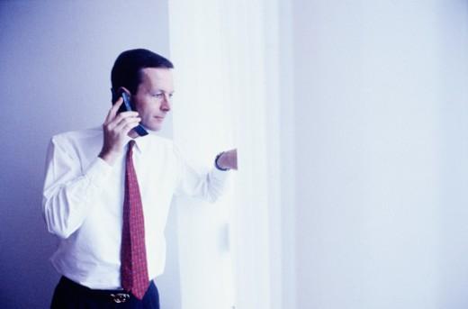 Businessman using mobile phone, looking through window : Stock Photo