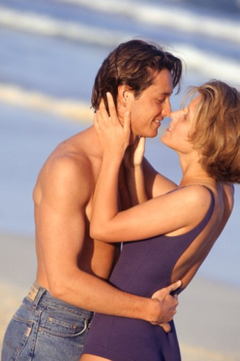 Stock Photo: 1598R-94680 Young couple embracing on beach
