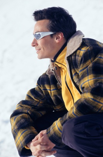 Stock Photo: 1598R-94724 Young man kneeling in snow, side view