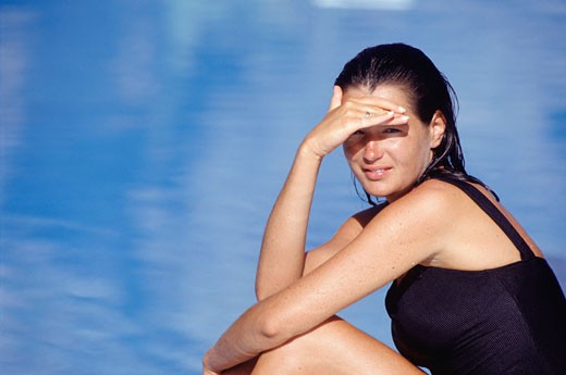 Stock Photo: 1598R-95033 Young woman sitting by pool, shielding eyes