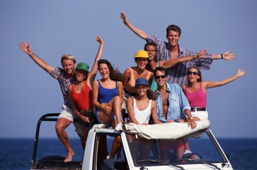 Stock Photo: 1598R-96427 Group of waving people in open 4x4,  portrait